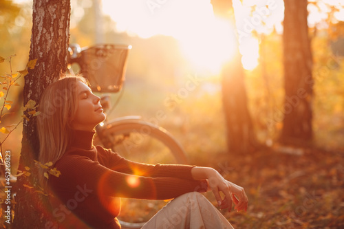 Canvas-taulu Happy active young woman sitting near vintage bicycle bike in autumn park at sunset
