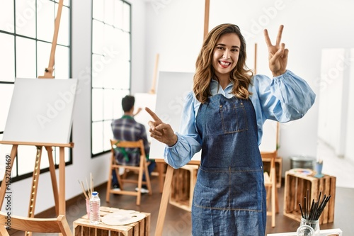 Slika na platnu Young artist woman at art studio smiling looking to the camera showing fingers doing victory sign