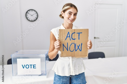 Canvas-taulu Young blonde woman at political election holding act now banner looking positive