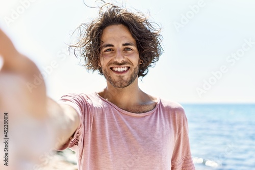 Fotografie, Obraz Young hispanic man smiling happy make selfie by the camera standing at the beach