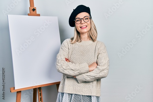 Billede på lærred Beautiful caucasian woman standing by painter easel stand happy face smiling with crossed arms looking at the camera