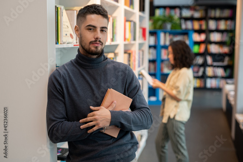 Foto Bearded young man with book standing in front of camera against female choosing