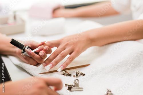 Brasilian latin mid woman manicure profesional puting to a client fiberglass nai Fototapeta