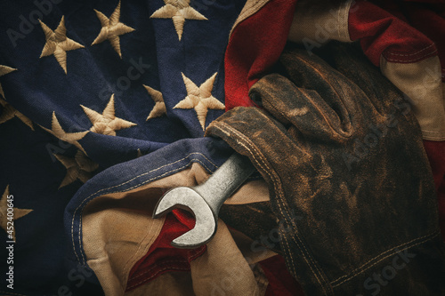 Obraz na plátně Worn work glove holding old wrench and US American flag