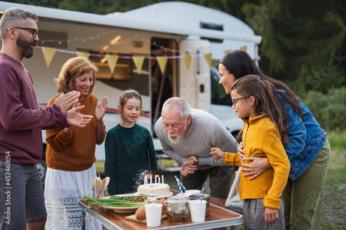 Multi-generation family celebrating birthday outdoors at campsite, caravan holiday trip Fototapeta