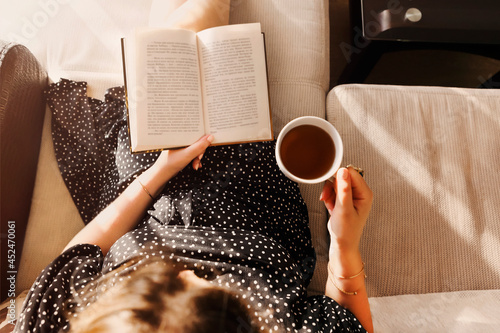 Photo from above of young woman in casual dress sitting with book and cup of tea Fototapet
