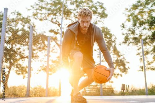 Fotografie, Obraz Young cool sunlit european sporty sportsman man 20s wear sports clothes doing ha