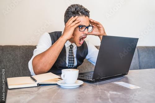Fotografija Hispanic businessman impressed with what appears on his laptop