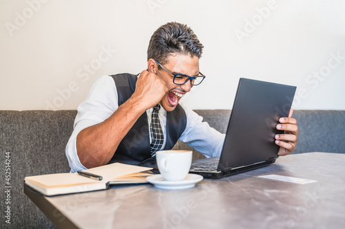 Hispanic businessman happy with what appears on his laptop Fototapeta