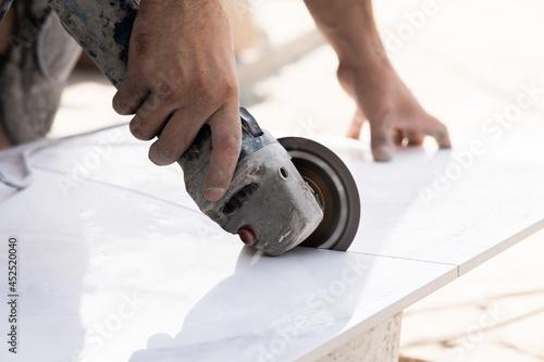 Billede på lærred Worker cutting stone with grinder.