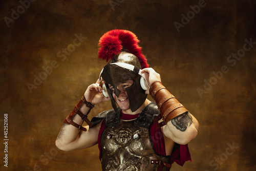 Tela Portrait of medieval person, young man, warrior or knight in war equipment isolated on vintage dark background