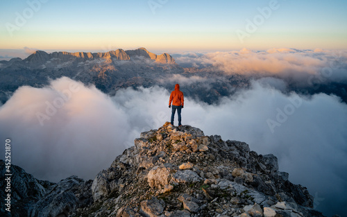 Fotografia A hiker stands on the ridge watching the valley being flooded by clouds at sunset