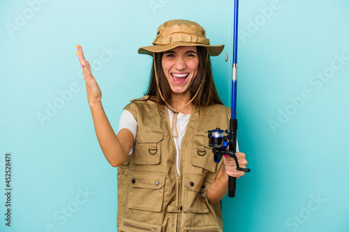 Fototapeta Young caucasian fisherwoman isolated on blue background receiving a pleasant surprise, excited and raising hands