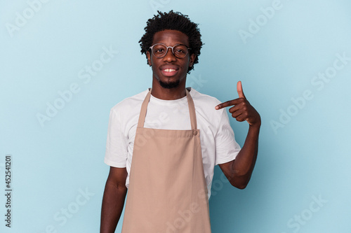 Wallpaper Mural Young african american store clerk isolated on blue background person pointing b