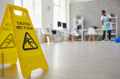 Foto Close up plastic caution sign with figure that slips and falls warning us of wet slippery office floor