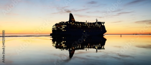 Fotografering Large white cruise liner (passenger ship) sailing in the Baltic sea at sunset