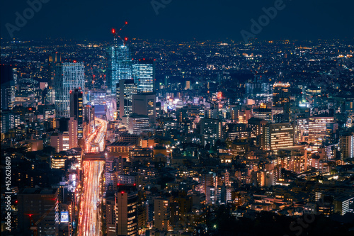 Light trails in long exposure at night on a large artery of traffic in Tokyo metropolis -View from above at Mori Tower observation deck at Roppongi Hills business center in Tokyo, Japan Fototapeta