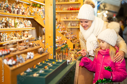 Fototapeta premium Female customers staring at counter of kiosk with figures for creating miniature Christmas scenes. High quality photo