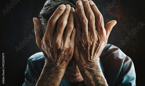 Canvas Print senior man covering his face with his hands.vintage tone