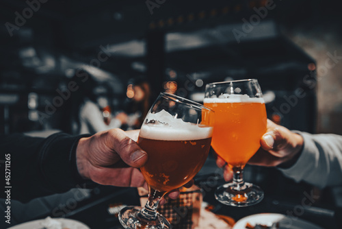 Платно two glass of beer in hand. Beer glasses clinking in bar or pub