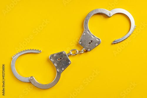 Fotografija Opened handcuffs on yellow background.