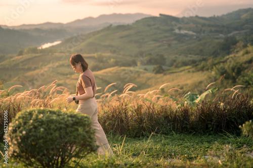 Fototapeta solo woman travel take photo and sightseeing sunrise on mountain at thailand