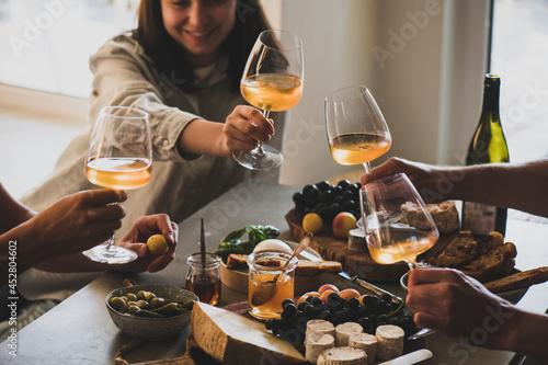Fotografie, Obraz Glasses of white orange or rose wine in peoples hands