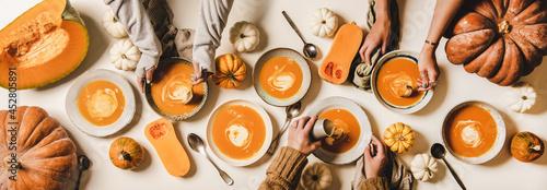 Obraz na plátně Flat-lay of female hands having dinner with fall pumpkin soup