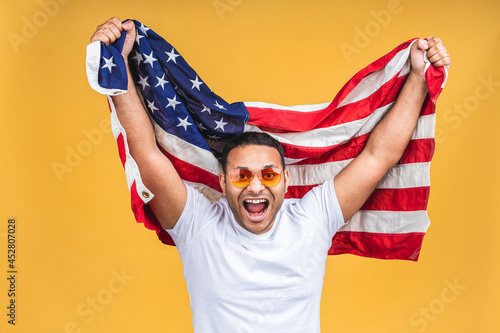 Photo of cheerful american african indian man protester raise american national flag black people revolution love all human beings express unity solidarity isolated over yellow background Fototapet