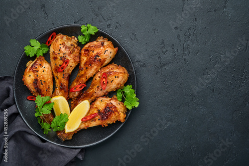 Cuadros en Lienzo Grilled chicken drumsticks or legs or roasted bbq with spices and tomato salsa sauce on a black plate