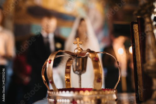 Canvas Wedding crown with bride and groom on blurred background in the church