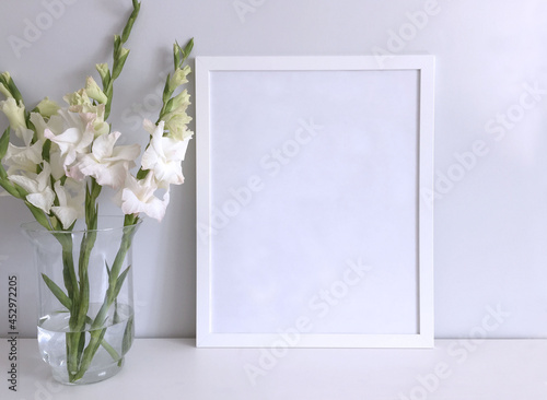 Wallpaper Mural A frame is a template for a photo or picture on a white table surface with a bouquet of white gladioli in a large glass vase next to it