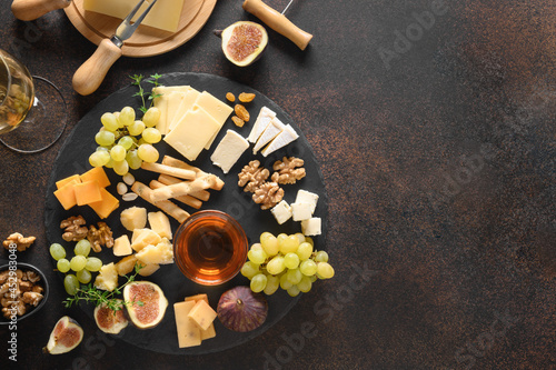 Fotografie, Obraz Cheese platter with grapes, nuts, figs on a brown background