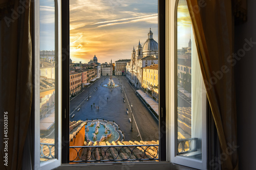 Fotografie, Obraz View through an open window of a room overlooking Piazza Navona at sunset in Rome, Italy