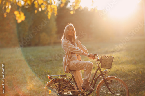 Slika na platnu Happy active young woman riding bicycle in autumn park.