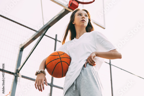 Fototapeta Portrait of young female basketball player