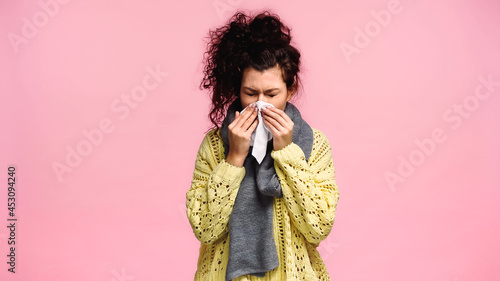 Canvas Print sick woman with closed eyes sneezing in paper napkin isolated on pink