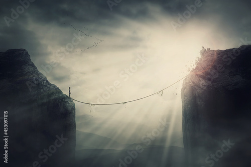Person on the edge of precipice determined to overcome the obstacle by passing an old slackline bridge Fototapet