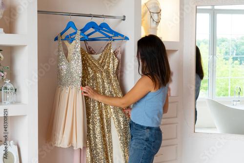 Brunette woman standing at wardrobe in room and choosing glamorous evening dress Fototapet