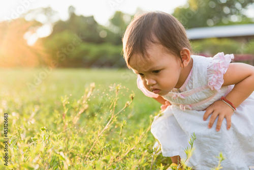 A little girl in the lawn looks at the spider closely at sunset Fototapeta