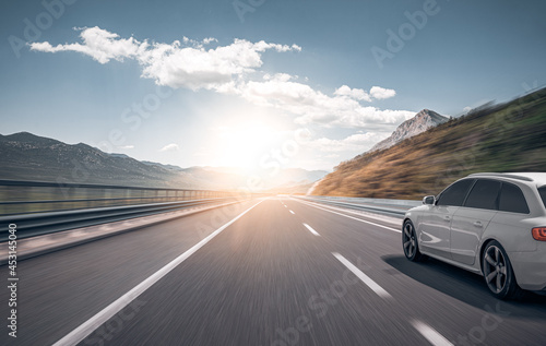 White car on a scenic road. Car on the road surrounded by a magnificent natural landscape.