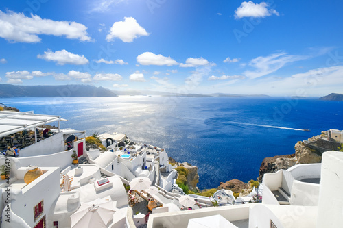 Fotografiet The whitewashed hillside town of Oia, Greece, filled with cafes and hotels overlooking the Aegean Sea and Caldera