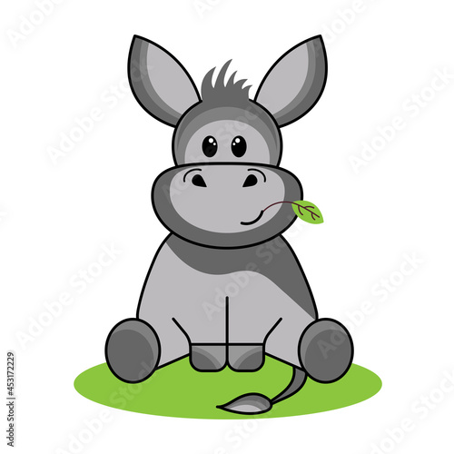 Fototapeta funny friendly donkey Eeyore sits in a clearing and chews an autumn leaf