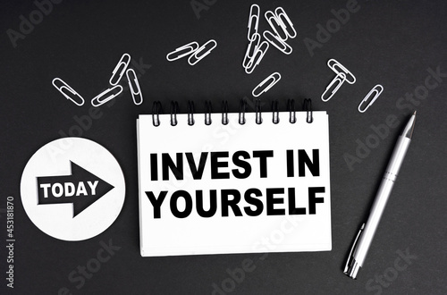 On a black background, a round plate - Today and a notebook with the inscription - INVEST IN YOURSELF