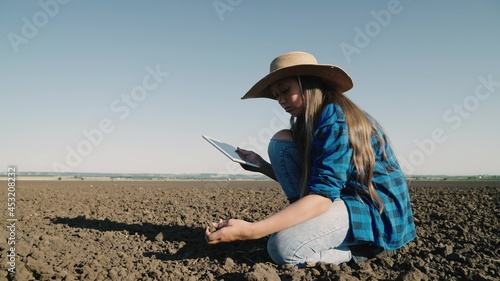 Fotografia Agriculture, an agronomist with a tablet checks in the field fertile land, organ