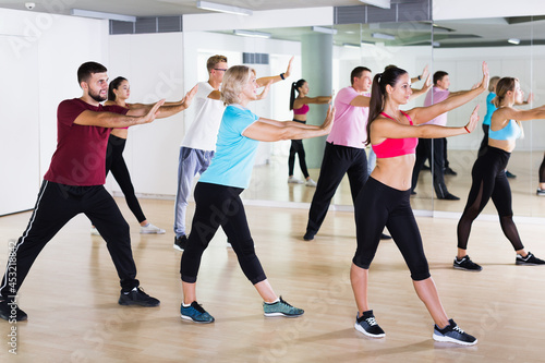 Fotografia, Obraz Positive people of different ages studying zumba dance elements in dancing class