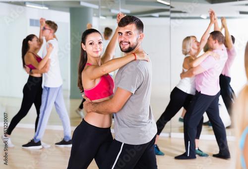Obraz na plátne Dancing positive european couples learning salsa at dance class