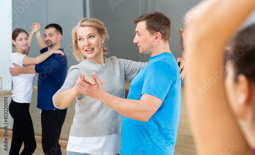 Fotografie, Obraz Cheerful middle aged woman learning to dance waltz with partner in dancing class