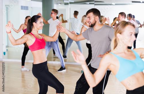 Fototapeta Young men and women dancing swing in dance class