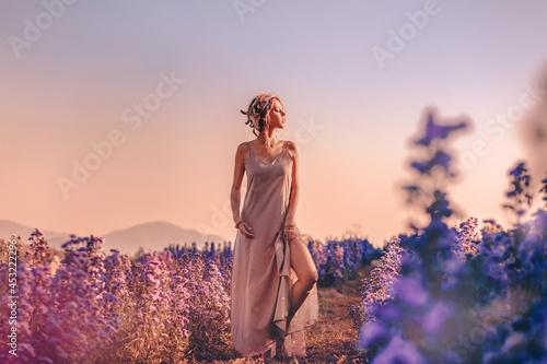 beautiful young stylish woman posing on the field at sunset Fototapet